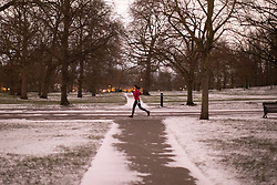 © Licensed to London News Pictures. 08/02/2021. London, UK. A woman exercises in Greenwich Park during a snow shower. Snow is expected for large parts of the UK and a yellow weather warning is in place in parts of England as Storm Darcy hits the UK. Photo credit: George Cracknell Wright/LNP