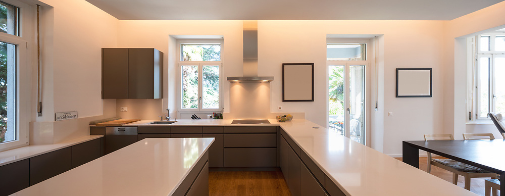 Modern kitchen in a period villa with window and parquet. White counters and brown doors. Nobody inside
