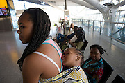 "A young African mother allows her sleeping baby some well-earned rest at Heathrow Airport's Terminal 5. In the departures concourse the mum and her child await their check-in zone to open in this international aviation hub in West London. The infant sleeps soundly, wrapped to its mother's back in the traditional manner for carrying children in the developing world. It is a simple scene of everyday care for one's child and airport operator spent £4.3 billion on Terminal 5 which has the capacity to serve around 30 million passengers a year. From writer Alain de Botton's book project ""A Week at the Airport: A Heathrow Diary"" (2009)."