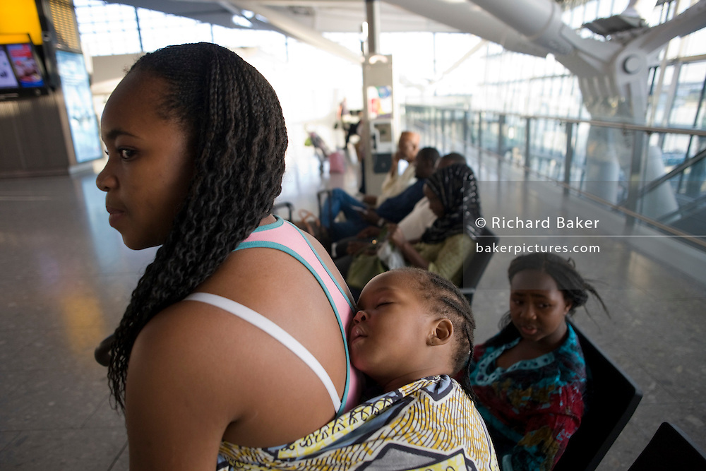 """A young African mother allows her sleeping baby some well-earned rest at Heathrow Airport's Terminal 5. In the departures concourse the mum and her child await their check-in zone to open in this international aviation hub in West London. The infant sleeps soundly, wrapped to its mother's back in the traditional manner for carrying children in the developing world. It is a simple scene of everyday care for one's child and airport operator spent £4.3 billion on Terminal 5 which has the capacity to serve around 30 million passengers a year. From writer Alain de Botton's book project """"A Week at the Airport: A Heathrow Diary"""" (2009)."""