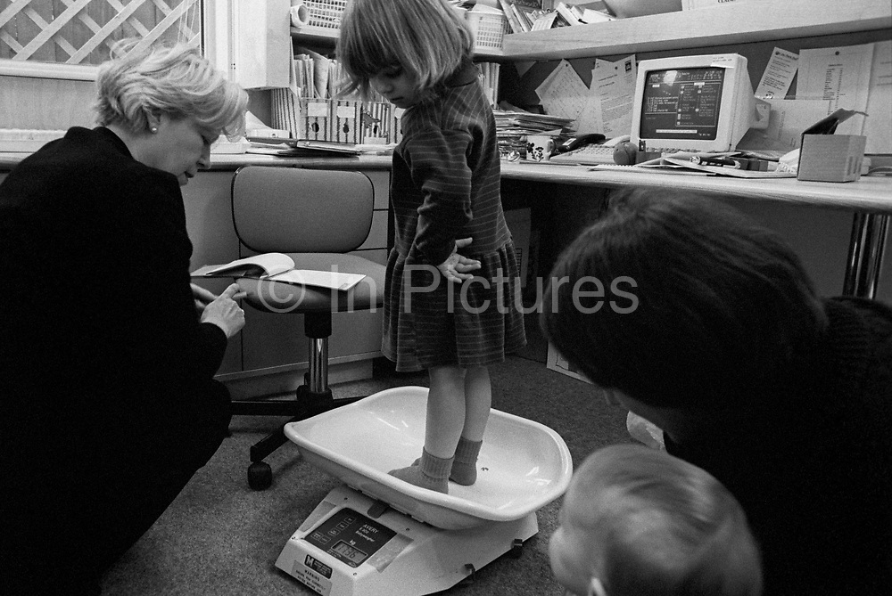 As a mother and younger brother look on, a 4 year-old girl has her weight checked by a local health visitor on scales in a south London childrens' clinic. Looking over her shoulder, the girl notices the reading on the scales that tell us she is 17.36 kilos (38lbs US) which is a healthy weight for a young, growing body. As her mummy and young brother look on, the community health visitor writes this progress into the child's personal health book, updated with her vital statistics since the day of her birth.