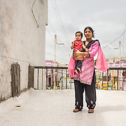 CAPTION: Mamta Chouhan, with her infant daughter, on the roof of her LIG house. The pilot has not only reduced temperatures, it has also fixed water leakage problems. LOCATION: Pink City, Indore, Madhya Pradesh, India. INDIVIDUAL(S) PHOTOGRAPHED: Arya and Mamta Chouhan.