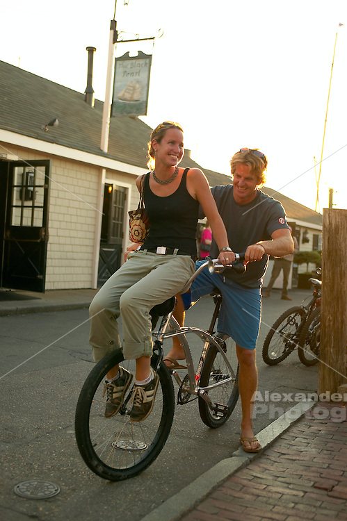 Christian Schlebach convinces Megan Burns to ride on the handle bars of his beach cruiser bike on Bannister's wharf in downtown Newport, RI