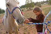 """09 SEPTEMBER 2007 -- ST. MICHAELS, AZ: JESSICA SMITH, 7, from Brimhall, NM, gives some grass to her mustang, Lightning, before the mustang was raced in a traditional Navajo Horse Race in the summit area of the Navajo Indian reservation about 10 miles west of St. Michaels, AZ. Traditional horse racing is making a comeback on the Navajo reservation. The races are run on improvised courses that vary depending on the local terrain. Use of saddles is optional (except in the """"Cowhand Race"""" which requires a western style saddle) and many jockeys ride bareback. The distances vary from one mile to as long as thirty miles. Traditional horse races were common until the 1950's when they fell out of favor, but there has been a resurgence in traditional racing since the late 1990's and now there is a traditional horse racing circuit on the reservation.  The race was organized by the Begay family of Steamboat, AZ and run on private land about three miles from a paved road.   Photo by Jack Kurtz"""