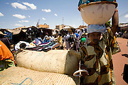 Woman carrying a bowl passes by one of the markets that surround Mopti's harbour. At the confluence of the Niger and the Bani rivers, between Timbuktu and Segou, Mopti is the second largest city in Mali, and the hub for commerce and tourism in this west-african landlocked country.