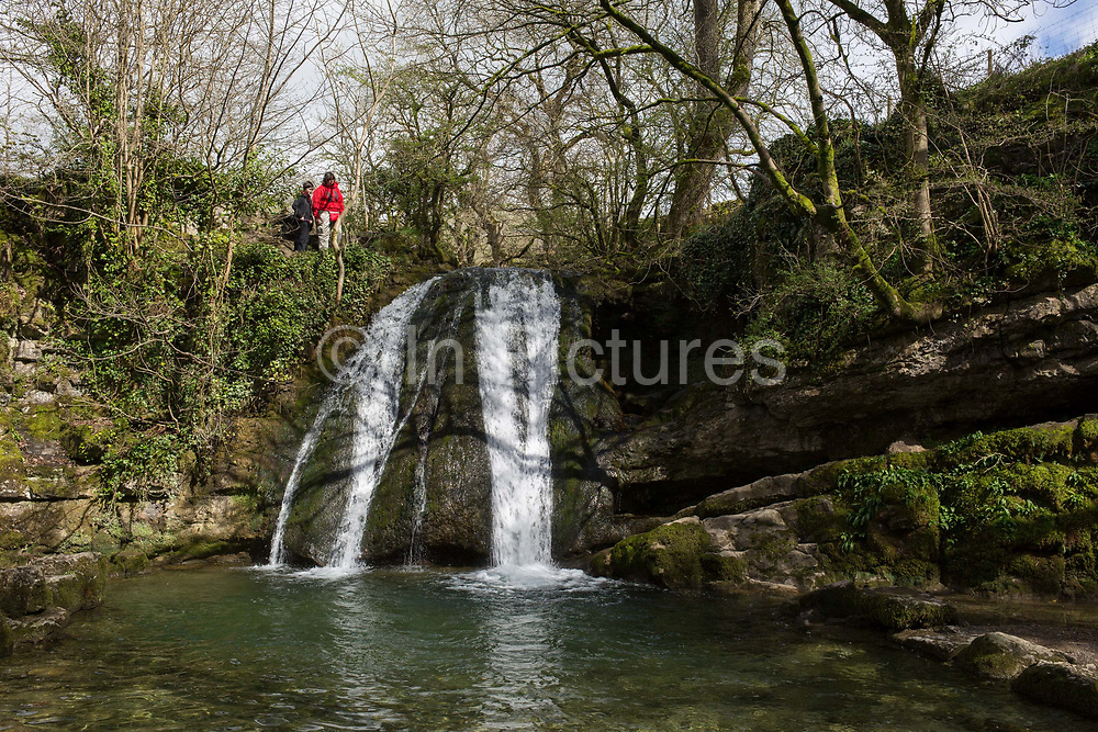 Walkers admire the Yorkshire Dales waterfall called Janets Foss on 12th April 2017, in Malham, Yorkshire, England. Janets Foss is a small waterfall in the vicinity of the village of Malham, North Yorkshire, England. It carries Gordale Beck over a limestone outcrop topped by tufa into a deep pool below. The pool was traditionally used for sheep dipping, an event which took on a carnival air and drew the village inhabitants for the social occasion. The name Janet sometimes Jennet is believed to refer to a fairy queen held to inhabit a cave at the rear of the fall. A foss is an old Norse word meaning waterfall.