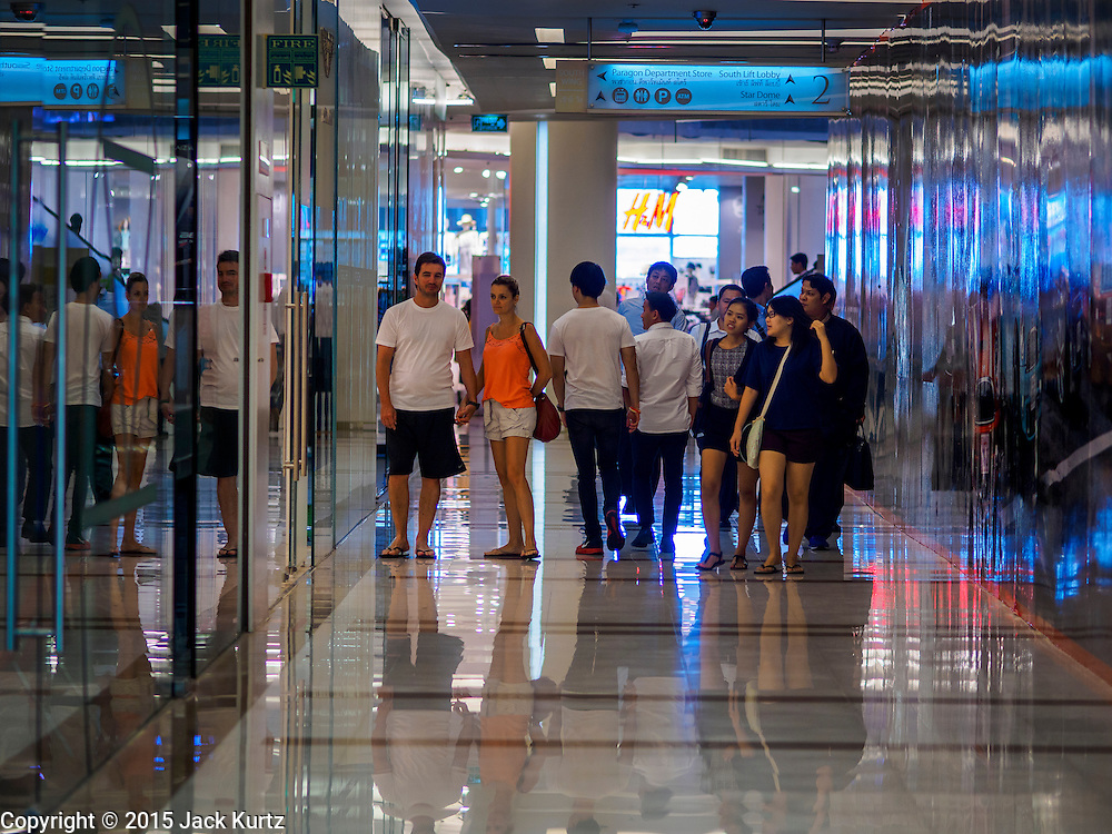 20 MAY 2015 - BANGKOK, THAILAND:  Shoppers walk through Siam Paragon mall in Bangkok. Bangkok's malls consume more electricity than some provinces. Siam Paragon, a popular high end mall in central Bangkok, consumes nearly twice as much electricity at the northern province of Mae Hong Son. Thais and foreigners alike flock to the malls in Bangkok, which are air conditioned. Most of the electricity consumed in Bangkok is generated in Laos and Myanmar. In 2013, the Bangkok Metropolitan Region consumed about 40 per cent of the Thailand's electricity, even though the BMR is only 1.5 per cent of the country's land area and about 22 per cent of its population.  PHOTO BY JACK KURTZ