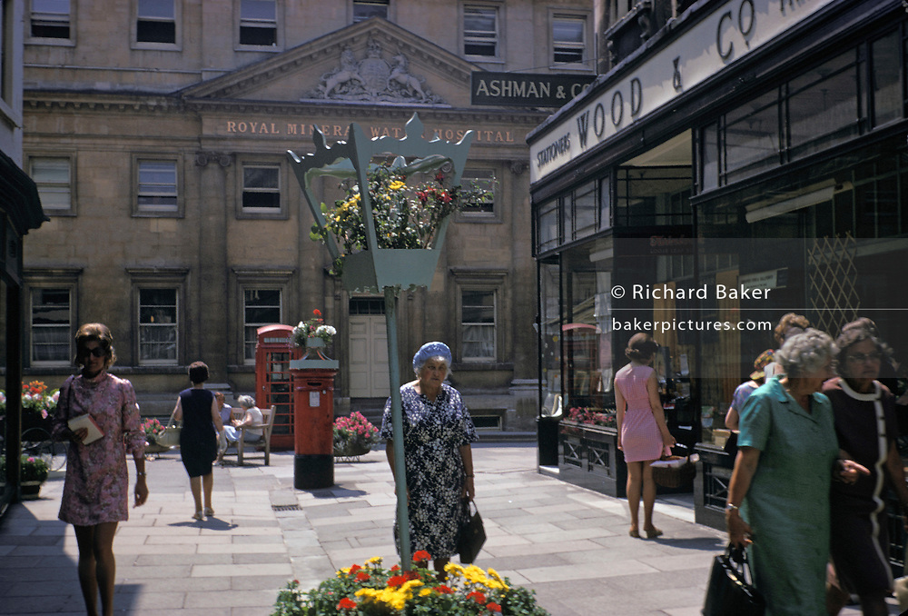 A 1970s street scene showing shoppers and pedestrians on the corner of Upper Borough Walls and Old Bond Street and the architecture of the Royal Mineral Water Hospital (now the Royal National Hospital of Rheumatic Deseseases), in central Bath, on 20th August 1971, in Bath, Somerset, England.