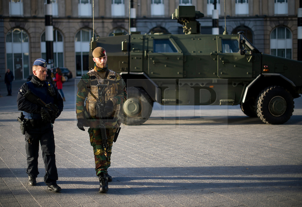 """© Licensed to London News Pictures. 23/11/2015. Brussels, Belgium. Belgian military walk past a military vehicle while patrolling Brussels Central Station  where the city is currently on """"lockdown"""" amid """"imminent threat"""" of Paris-style bomb and gun attacks. Photo credit: Ben Cawthra/LNP"""