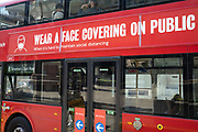 Public transport signs to wear a face covering or face mask while travelling by TfL buses on the day that it was announced that the Coronavirus lockdown measures are set to ease even further and the quiet city starts coming to an end, on 23rd June 2020 in London, England, United Kingdom. As of today the government has relaxed its lockdown rules, and is allowing some non-essential shops to open with individual shops setting up social distancing queueing systems.