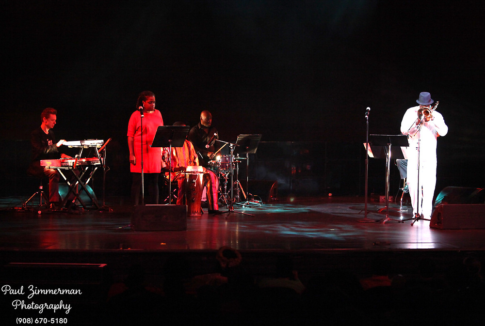 NEW YORK, NY - DECEMBER 30:  (L-R) Musician Carla Cook ( Red Dress) and Craig S. Harris ( White suite)  of the band Tailgater's Tails perform at the 5th Annual Regeneration Night Kwanzaa Celebration at The Apollo Theater on December 30, 2011 in New York City.  (Photo by Paul Zimmerman/WireImage)