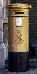 © Licensed to London News Pictures. 18/08/2012. Chiswick, UK A Royal Mail postbox painted gold in honour of Olympic Gold Medalist Pete Reed, Men's Fours Rowing; in Chiswick, London. The postoffice has painted the traditional red postboxes in medalists local areas gold, in celebration of the UK gold medals in London2012 Photo credit : Stephen Simpson/LNP