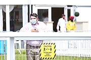 A spectator stands over a Social Distance sign - Mandatory by-line: Robbie Stephenson/JMP - 22/07/2020 - HORSE RACING - Bath Racecoure - Bath, England - Bath Races
