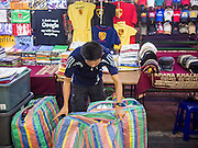 23 AUGUST 2014 - BANGKOK, THAILAND:        A Thai man sets up his stand selling clothes at a night sidewalk market on Sukhumvit Road near Soi 5 in the Nana section of Bangkok. The Thai military junta, formally called the National Council for Peace and Order (NCPO), has ordered street vendors off of the sidewalks in an effort to bring order to Bangkok's chaotic sidewalks. Vendors have complained that the new regulations are hurting them economically but largely complied with the military orders.    PHOTO BY JACK KURTZ