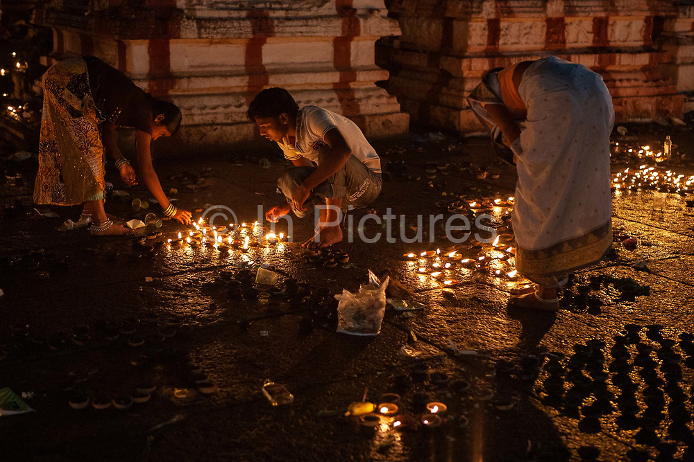 People lighting candles in worship in Virupaksha temple in the UNESCO heritage site, ancient, holy village and Temple complex of Hampi on 4th December 2009, Karnataka, India. Hampi is one of Indias most famous landmarks, with numerous Hindu temples from the Vijayanagara Empire. .