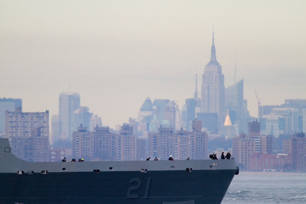 The USS New York built with steal salvaged from the World Trade Center Towers sails out to sea from the Sandy Hook Channel leaving the Navel Weapons Station Earle pier after being stuck in port due to a fierce   nor'easter storm that affected the area .  Behind the bow of the USS NY is New York City