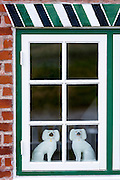 Traditional Staffordshire dog figurines in window of cottage house on Fano Island, South Jutland, Denmark