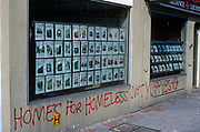 "Graffiti has been sprayed in red with aerosol on the wall of an estate agent in Herne Hill, South London England. ""Homes for the Homeless, not Yuppies"" it reads along with the Anarchists' Circle-A symbol, meaning that housing should be made available for families needing a roof over their heads, rather than overpricing properties for the middle-classes buying for profit and investment. We see the writing on the wall beneath pictures in windows of houses and flats in the SE24 area where prices are posted along with details of the buildings. The house-buying market climbs according to demand in areas of the city such as this, forcing up values which are out of reach to ordinary, working people unable to climb the property ladder."