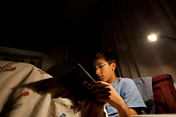 "Santiago Gonzalez, 13, reads a programming text book in bed before falling asleep, Littleton, Colo., Aug. 29, 2011. Gonzalez is a full-time college student at the Colorado School of Mines, an engineering university. He wakes up at 5:30 a.m. every morning during the academic semester to develop iPad and iPhone applications in a programming language called Objective C, which he learned from a textbook when he was 9 years old. That textbook and 86 similar volumes including Applied Finite Mathematics, Infinity in Your Pocket, Programming in C++ and Dictionary of Physics, sit in a glass-fronted bookcase opposite his bed. ""Exceptionally gifted"" is the commonly used phrase for kids as smart as Gonzalez."