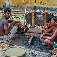 A blacksmithand his sons wait for the next customer at  his outdoor stall near Dhaka, Bangladesh.