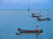 18 JULY 2016 - KUTA, BALI, INDONESIA:  A man rows his small boat back to shore at Pasar Ikan pantai Kedonganan, a fishing pier and market in Kuta, Bali. He works shuttling supplies and crewmen out to larger boats.   PHOTO BY JACK KURTZ