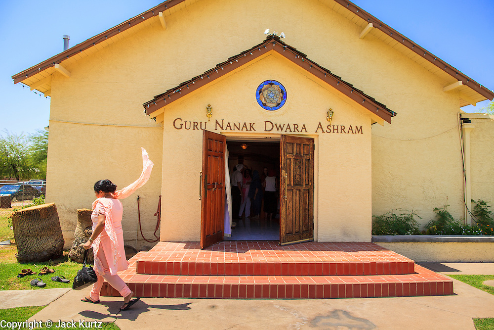 12 AUGUST 2012 - PHOENIX, AZ: A woman leaves the temple after Sunday services at the Guru Nank Dwara Ashram Sikh temple in central Phoenix. Guru Nank Dwara Ashram is the oldest of three Sikh temples in the Phoenix area. There are about 1,500 Sikh families in the area. Memorials have been held throughout the week to honor the Sikhs killed in the mass shooting in Wisconsin last week. Sunday's service included several mentions of the massacre and was attended by a number of people active in the Phoenix interfaith community.  PHOTO BY JACK KURTZ