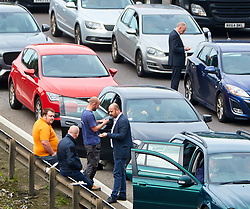 © Licensed to London News PiPeople wait by their cars on closed carriageway of the M1 near Hanslope between junctions 15 and 14. The road has been closed since 7:30am this morning, trapping hundreds of people, as the police deal with a suspicious item found under a bridge. The location is very near to Hanslope Park, home to Her Majesty's Government Communication Office (HMGCC0, part of FCO.  Photo credit: Cliff Hide/LNP