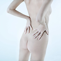 studio shot picture of the back young beautiful naked caucasian woman lying on a white floor