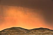 Storm light at sunrise over rolling hills of mixed-grass native prairie<br />Grasslands National Park<br />Saskatchewan<br />Canada