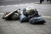 Plastic bags of uncollected rubbish on London street, England