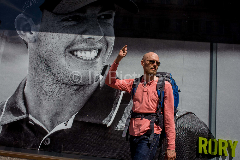 Man passes a Nike retail poster of Northern Irish golfer Rory McIlroy, in central London. The bald-headed man gestures to others next to the sports hero's name in the bottom corner. The scene has a theme of smiles and smiling faces with the teeth of the British golfing hero, sponsored by the Nike brand.