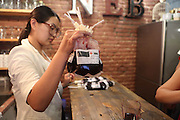"""BENXI, CHINA - JUNE 26: (CHINA OUT) <br /> <br /> Blood Bag Drink<br /> <br /> A woman makes the """"Blood Bag"""", a crimson beverage offered with two flavors of blueberry and cranberry on June 26, 2014 in Benxi, Liaoning province of China. """"Blood Bag"""", a crimson beverage was marked by the sign of """"Blood Type Energy Supply"""" as well as the symbol of Red Cross and the beverage was for sale with the price of 30 RMB (about 4.8 USD) in China's northeast city of Benxi. <br /> ©Exclusivepix"""