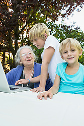 Grandmother and her two grandsons with laptop