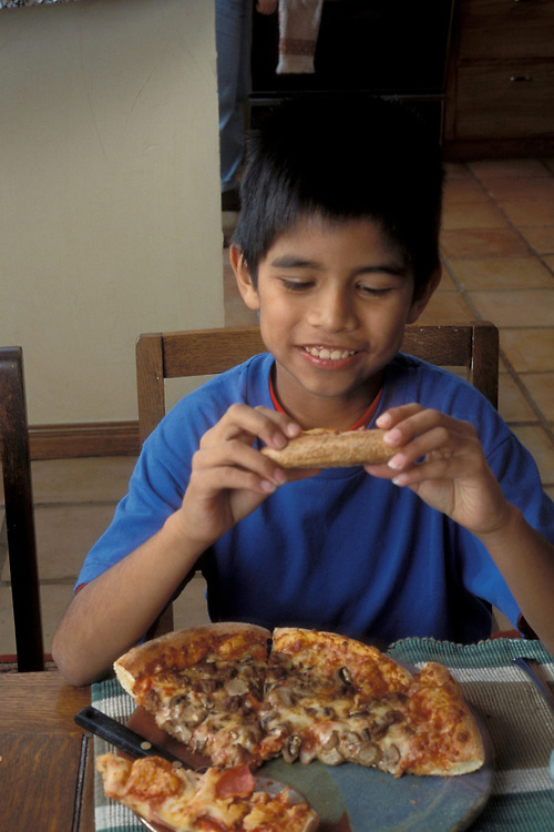 Young Hispanic boy,10 year old, eating pizza at home at dinner table.  Model Release.<br /> ©Bob Daemmrich
