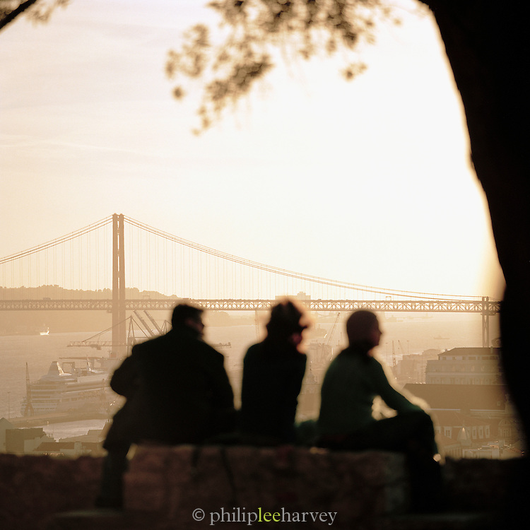 People sit overlloking the city of Lisbon and the 25th of April Bridge, Portugal