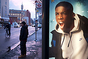 Advertising at a bus stop on Whitechapel High Street. An Asian youth waits in the snow beside a poster which appears to be shouting a him. Perhaps a sign of a disaffected youth in this relatively poor part of London which is primarily a Muslim area.