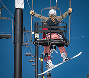 A snowboarder rides the Breezeway Chair at Monarch Mountain on a sunny March day.