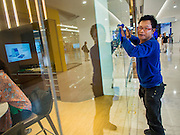"""27 MARCH 2015 - BANGKOK, THAILAND: A worker cleans a window in a bank in """"EmQuartier,"""" a new mall in Bangkok. """"EmQuartier"""" is across Sukhumvit Rd from Emporium. Both malls have the same corporate owner, The Mall Group, which reportedly spent 20Billion Thai Baht (about $600 million US) on the new mall and renovating the existing Emporium. EmQuartier and Emporium have about 450,000 square meters of retail, several hotels, numerous restaurants, movie theaters and the largest man made waterfall in Southeast Asia. EmQuartier celebrated its grand opening Friday, March 27.    PHOTO BY JACK KURTZ"""