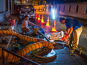 """27 MARCH 2013 - BANGKOK, THAILAND:  Men work at upgrading sewer lines in a residential neighborhood in Bangkok. Thailand's economic expansion since the 1970 has dramatically reduced both the amount of poverty and the severity of poverty in Thailand. At the same time, the gap between the very rich in Thailand and the very poor has grown so that income disparity is greater now than it was in 1970. Thailand scores .42 on the """"Ginni Index"""" which measures income disparity on a scale of 0 (perfect income equality) to 1 (absolute inequality in which one person owns everything). Sweden has the best Ginni score (.23), Thailand's score is slightly better than the US score of .45.  PHOTO BY JACK KURTZ"""