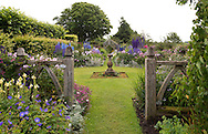 An oak gate leading to The Compass Garden and a large collection of brightly coloured Delphiniums at Wollerton Old Hall, Wollerton, Market Drayton, Shropshire, UK