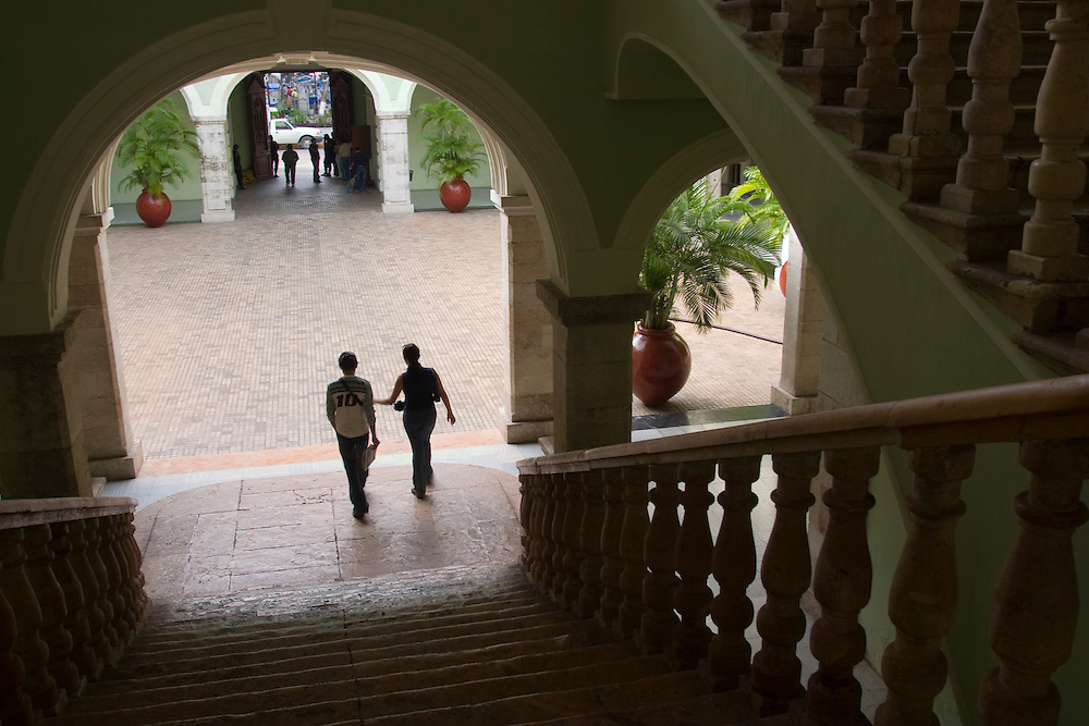 Mexico, Yucatan, Merida, couple descending staircase in colonial mansion with art gallery