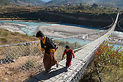 Bhutan, a woman and a young monk crossing the longest suspension bridge in Bhutan in the Punakha valley.
