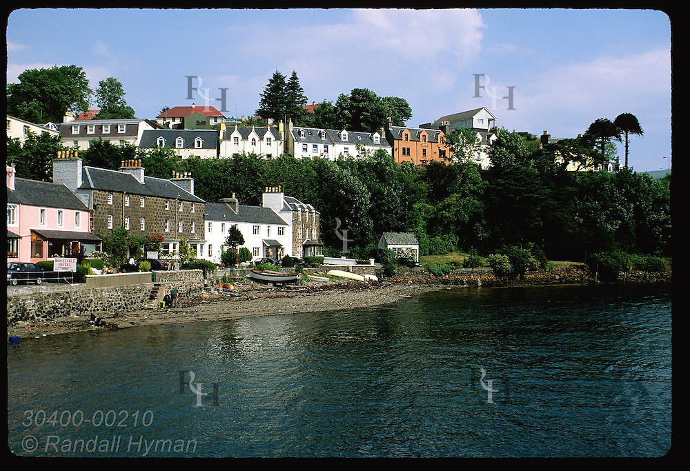 Buildings line the wharf and bluff of Portree's main harbor on a sunny July morn; Isle of Skye. Scotland