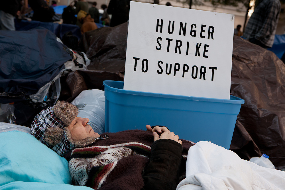 """A man with his eyes closed lies down in front of a sign reading """"Hunger strike to support."""""""