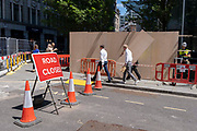 City workers walk past a new plyboard construction hoarding in the City of London, the capitals financial district, on 8th June 2021, in London, England.