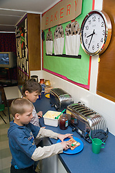 Children spreading butter on slices of toast at school breakfast club,