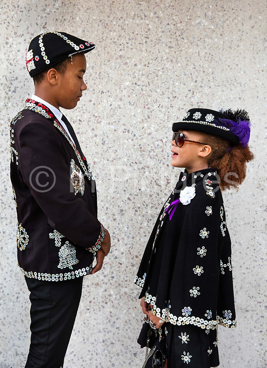 Prince Harris and Princess Ruby of Highgate attending the Pearly Kings and Queens Harvest Festival celebrations at Guildhall Yard. The annual event features early English entertainment including maypole dancing, Morris dancers and a marching band. The Chelsea pensioners & all the mayors of London take part in this traditional London event.<br /> The London tradition of the Pearly Kings and Queens began in 1875, by Henry Croft. Inspired by the local Costermongers, a close-knit group of market traders who looked after one another and were recognisable by buttons sewed onto their garments, Henry went out on the streets to collect money for charity, wearing a suit covered in pearl buttons to attract attention. When demand for his help became too much, Henry asked the Costermongers for assistance, many of whom became the first Pearly Families. Today, around 30 Pearly Families continue the tradition to raise money for various charities.