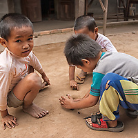 Tree boys playing with marbles in a street.