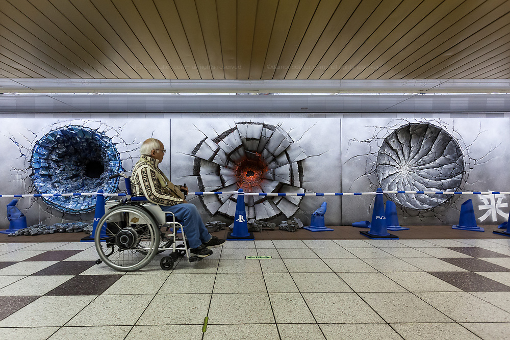 A man in a wheelchair passes three craters in a wall advertising the Jump Force video game for Play Station, X-box and Window PC in Shinjuku Station, Tokyo, Japan. Friday February 22nd 2019. Jump Force  game brings together all the most popular characters from the Shonan Jump manga comics.and was released on February 15th. The punch wall represents the effect of a power punch from characters Son Goku of Dragonball, Naruto and Luffy from One Piece and runs to February 24th