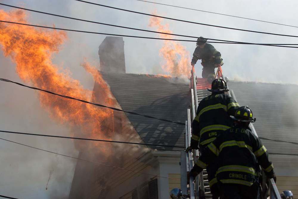 Milton, MA 03/08/2012.A Quincy firefighter evacuates the roof while fighting a 3 alarm house fire at 589 Adams St. in Milton on Thursday afternoon..Alex Jones / www.alexjonesphoto.com